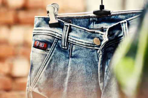 selective focus photography of blue denim bottoms hanged on gray metal hanger