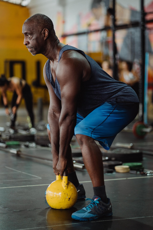man lifting kettlebell weights